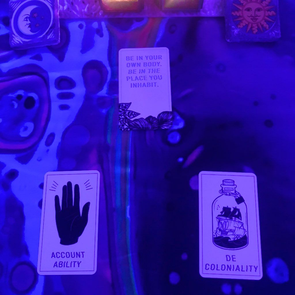 """Three cards under blacklight,  At the top, a card with the words """"Be in your own body.  Be in the place you inhabit."""" On the bottom left, a hand and the word Accountability.  On the bottom right, a ship in a bottle with a lock on it, and the word Decoloniality."""