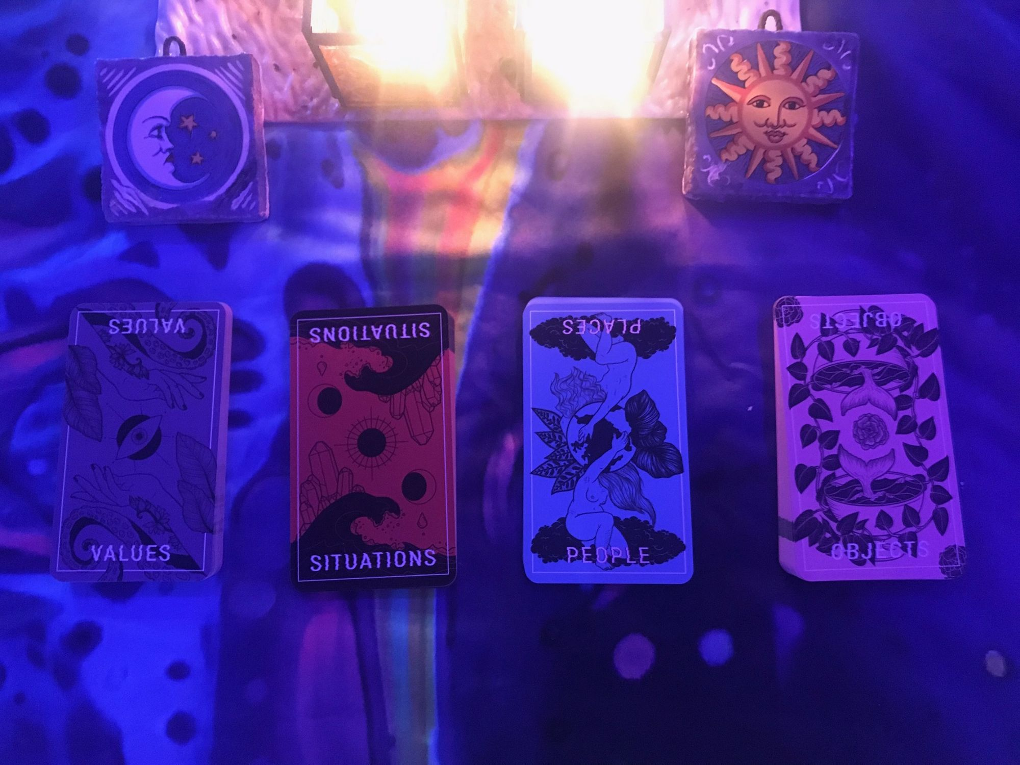 Four cards, with the words Values, Situations, Places, and Objects.  Above them, two small ceramic tiles with a moon on the left and a sun on the right, and candlelight between them.