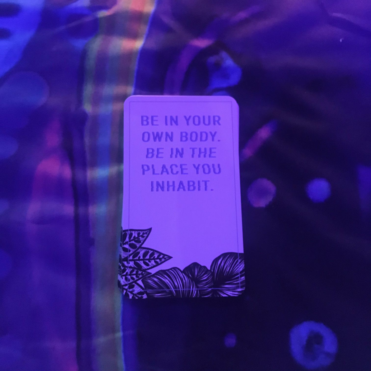 """A card on a colorful reading cloth, under black light, with the words """"Be in your own body.  Be in the place you inhabit."""""""